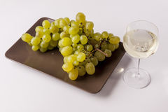 White grapes with a glass of white wine -white bac. White grapes with a glass of white wine on white background Stock Photography