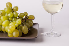 White grapes with a glass of white wine -white bac. White grapes with a glass of white wine on white background Royalty Free Stock Photos