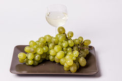 White grapes with a glass of white wine -white bac. White grapes with a glass of white wine on white background Stock Photo