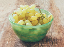 White grapes in a green bowl on old rustic wooden Board cracked Royalty Free Stock Photo