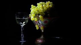 White grapes on an old painted bowl on a black background with a glass of wine. (Rotating) stock video
