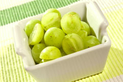 White grapes in small bowl on green background. White grapes in small white bowl on green background royalty free stock image