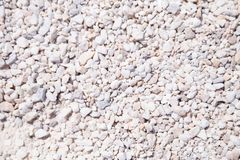 White gravel coating. The texture of white stone minerals crumb. White abstract background. Gravel coating tracks. Top view royalty free stock photo