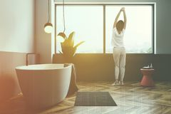 White and gray bathroom, tub and and window, woman. Woman in minimalistic bathroom interior with white and gray walls, wooden floor, large window, white bathtub royalty free stock images