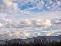 White and gray clouds in a blue sky with foreground. Multiple types of white and gray clouds in a deep blue sky with trees and mountains in the low foreground Stock Images