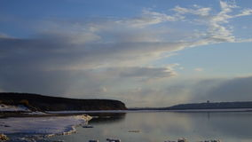 White gray clouds sail over a big lake. In the surface of the water reflected the passing clouds. Water surface start to break fre. E from the ice. It is getting stock footage