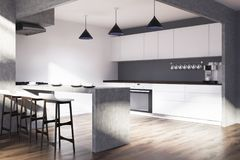 White and gray kitchen with a bar stand side. Modern kitchen interior with white and gray walls, a wooden floor and white cupboards and countertops. Side view Royalty Free Stock Photos