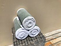 White with a gray stripe towels rolled into a roll in the spa on a wicker cabinet on a beige background. 