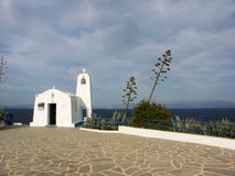 White greek chappel with high agave plant Royalty Free Stock Photo