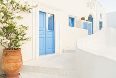 White Greek house with blue door and flower pot Stock Photography