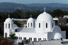 White Greek Orthodox Church with three crosses mountain hills in background stock images