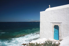 A white Greek ortodox churche in Mykonos. With blue sea on the background Royalty Free Stock Image