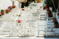 White Greek stairs with tables and chairs. Typical Greek street Stock Photos