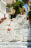 White Greek stairs with tables and chairs. Typical Greek street Royalty Free Stock Photo