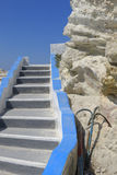 White Greek stone steps. Closeup of blue and white stone steps next to rocks with blue sky background, Greece Royalty Free Stock Photos