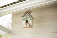 White and Green Bird House. Small bird house hanging from the roof of a house or garage stock photo