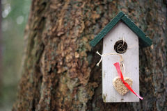 White and green birdhouse with hanging heart made from seeds Royalty Free Stock Image