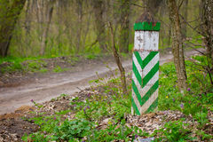 White green boundary post at a spring forest ground road Royalty Free Stock Photography