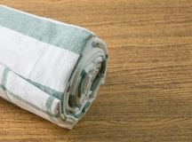 White and Green Kitchen Towel on Wooden Table Royalty Free Stock Photos