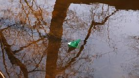 White, and green paper boat sails on the river. White, and green paper boat sails on river stock video footage