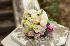 White green, pink and yellow and pink wedding bouquet with roses on the stone. Colorful image of beautiful nosegay Royalty Free Stock Photo