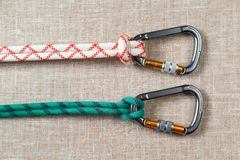 White and green ropes tied to two large aluminum professional carabiner for climbing. On textured fabric background Stock Photos