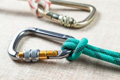 White and green ropes tied to two large professional carabiner for climbing. On textured fabric background Stock Photo