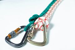 White and green ropes tied to two large professional carabiner for climbing. On white background Stock Photos