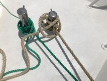 White and green strong fabric ship ropes, ropes tied to a ship, a boat on a white background royalty free stock photo