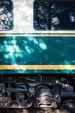 Side of Train side window wheels. White green train windows in shade. Passengers transportation window. Horizontal coach and wheel. green yellow white black Royalty Free Stock Images