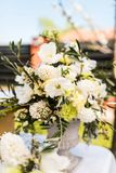 White and green variety of flowers in a large central table bouquet. Antique vase made of cement stock images