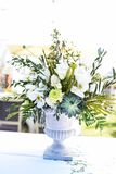 White and green variety of flowers in a large central table bouquet. Antique vase made of cement stock photo