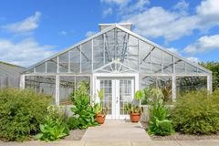 White greenhouse against blue sky with fluffy white clouds Royalty Free Stock Photo
