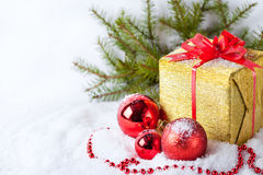 White greeting card with copy space for christmas with golden wrapped gift, fir branches and red ball on snow Royalty Free Stock Photo