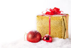 White greeting card with copy space for christmas or new year with golden wrapped gift and red ball on snow Stock Photo
