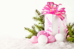 White greeting card with copy space for christmas or new year with a wrapped gift, fir branches and pink ball on snow.  Royalty Free Stock Image