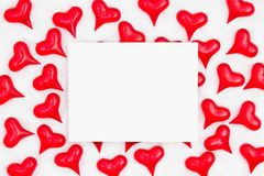 White greeting card with red hearts on white fabric background. With copy space for your message stock photo