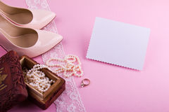 White greeting card with wavy edge. Beige leather shoes with high heel, greeting card and accessories on pink background. Stock Photos