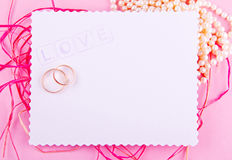 White greeting card with wavy edge is decorated with wedding rings on pink background. Stock Photos