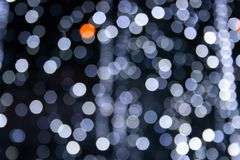 White and grey bokeh lights. Abstract background white and grey bokeh lights, frozen fountain in winter, cascade of sparks, cold feeling, coldness stock photos