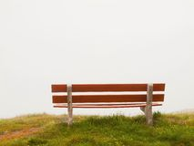White grey clouds in opposite of red wooden bench on meadow. September misty evening on the hill in Switzerland Alps. White grey clouds in opposite of red wooden Royalty Free Stock Image