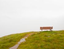 White grey clouds in opposite of red wooden bench on meadow. September misty evening on the hill in Switzerland Alps. White grey clouds in opposite of red Royalty Free Stock Photos