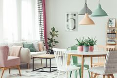 Modern pastel flat interior. White, grey and green chair at round table under pastel lamps in modern flat interior with sofa and pink armchair stock photo