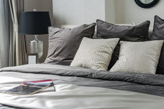White and grey pillows on bed. In modern bedroom interior Stock Image