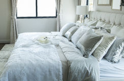 White and grey pillows on bed. In vintage style bedroom Royalty Free Stock Photography