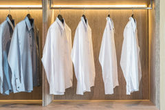White and grey shirts hanging in wardrobe Stock Images