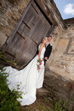 White and grunge. Young wedding couple against a grunge medieval wall royalty free stock images