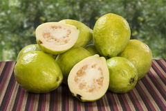 White guava cut in a alf on a plantation background. White guava cut in a alf in over some entire white guavas over a striped surface on a plantation background Royalty Free Stock Photography