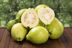 White guava cut in a alf on a plantation background. White guava cut in a alf in over some entire white guavas over a striped surface on a plantation background royalty free stock photo
