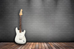 White guitar on gray wall. Guitar leaning against a gray brick wall Stock Images